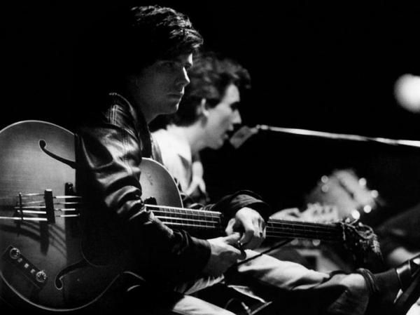 Stuart Sutcliffe sat, playing bass, with George Harrions in the background