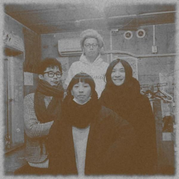 The Japanese rock band Mass Of The Fermenting Dregs stood in a group wrapped up for the cold winter weather.