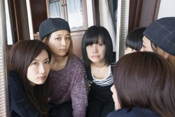 The female Japanese rock band photographed looking at and in a mirror.