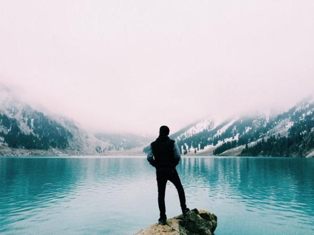 A man stood in the way of a teal blue mountain lake.