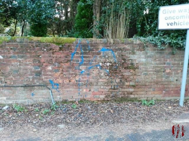 Brick wall of Cemetary next to the Drill Hall in Horsham with fairly bright blue paint daubed at random across it and the leaves on the tarmac in front of it.