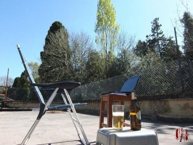 Folding chair in front of stool with laptop on top whilst in the foregorund in a half poured bottle of beer. The sky is completely blue and the sun streams down on to the trees in the background.
