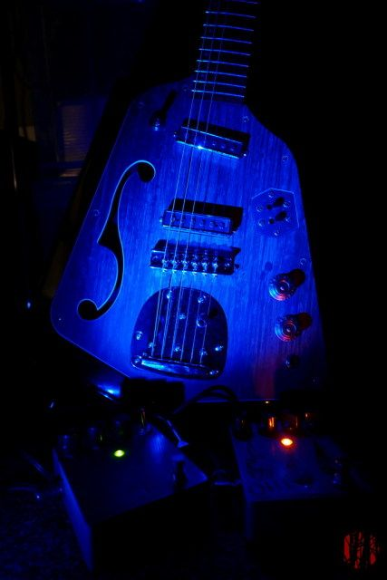 A semi-acoustic Eastwood Domino Guitar lit in blue, orange and green from the light of their on indicator LEDs