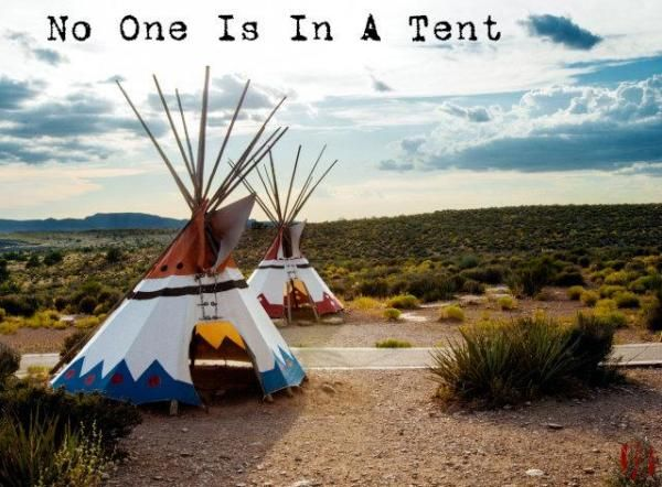 Photo of an empty teepee during the day on fairly flat terrain with low rises and mountains behind with caption 'No One Is In A Tent'.