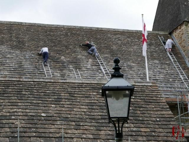 Men on ladders working on the roof of St Mary's Church Horsham with little regard for safety leaning off unsecured ladders