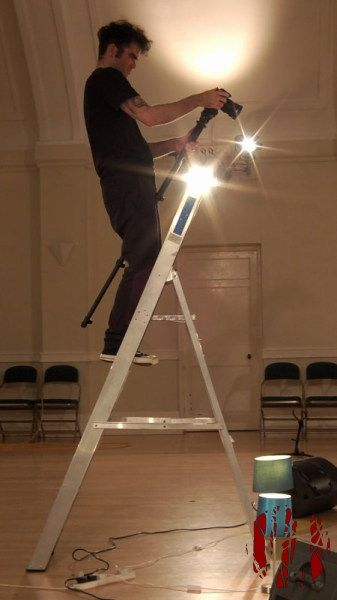 The director / cameraman of the Little White Blue video up a ladder filming the band with lights behind him flaring artistically.