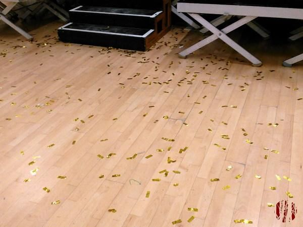 The wooden floor of a Community Hall covered in short strips of gold glitter which also extend beneath a portable stage.