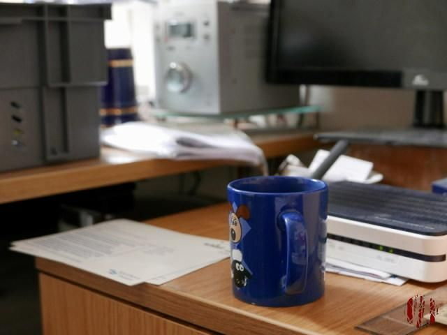 A blue mug on a two draw wooden filing cabinet with blurred background. Gromit from the Wallace & Gromit animations can be seen on the mug.