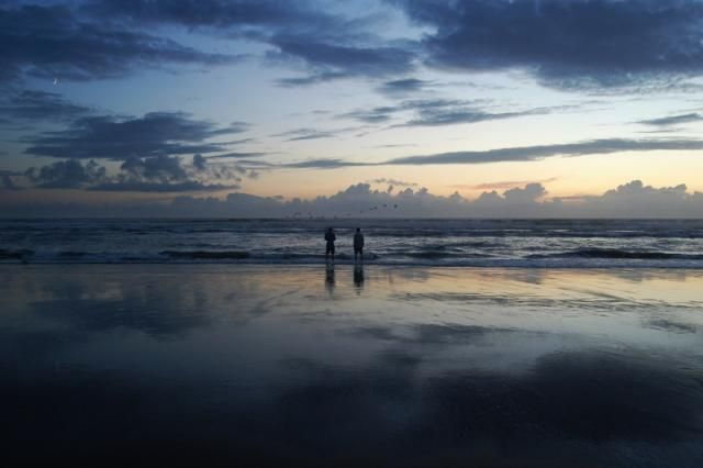 Two men standing at the sea's edge at sunset