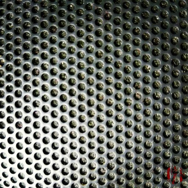 Close up of the honeycomb like grill of a small portable speaker unit.