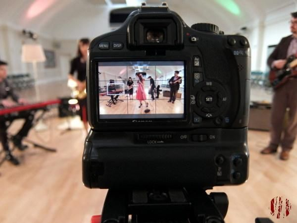 Function band Little White Blue seen through on the display of a digital camera being used to film a promotional video.