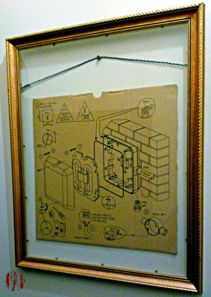 Photo of an expanded drawing printed on part of a cardboard box showing how to install a square emergency light with a glassless picture frame