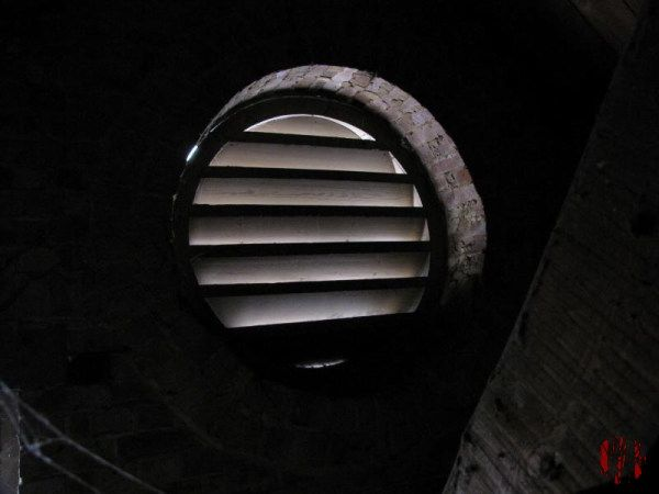Sunlight seen through the angled slats of a round ventilation opening about three feet across in a loft.