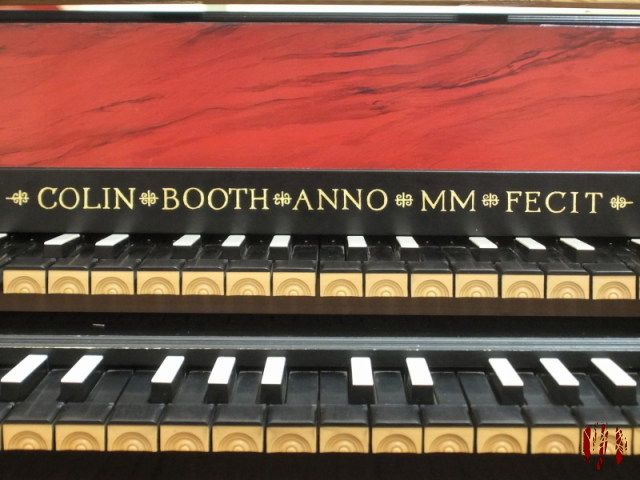 Keyboard of a harpsichord, all black except white tops to the sharp notes. The name of the maker, Colin Booth, is inscribed in gold along with date of manufacturer, MM or 2000 AD.