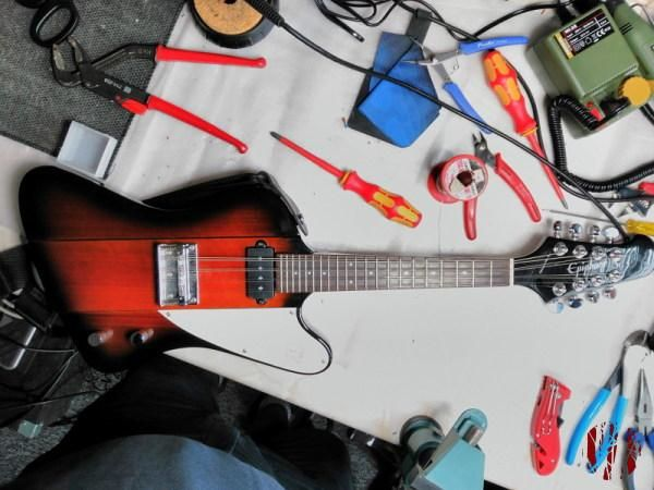 A solid body electric mandolin in the shape of a Gibson Firebird with various tools lying around it.