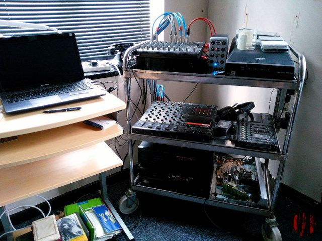 A tea trolley with two and four track cassette players as well as MiniDisc and digital audio tape machines next to a desk with a laptop computer. Cassettes are scattered round about.