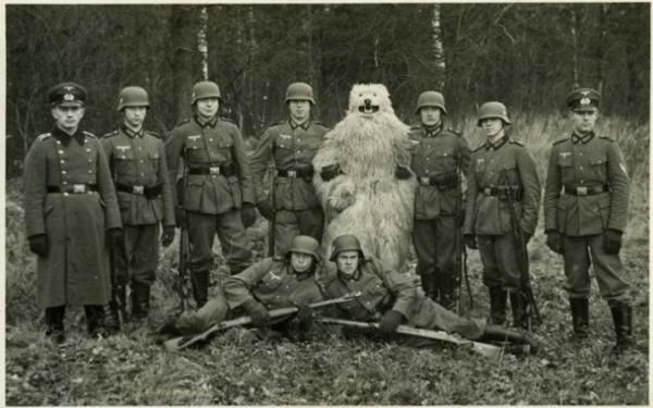 Photograph of a group of Second World War German troops and someone wearing a white bear suit with a cheery smile.