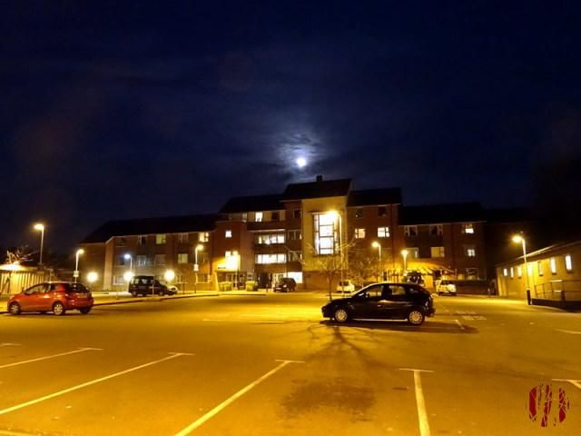 Bright moon through clouds in a deep dark blue evening sky over a large three and four storey care home with a car park with few vehicles in front bathed in the warm orange glow of artifical light